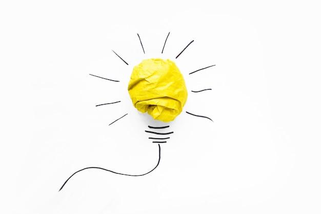 Pomysły biznesowe. kompozycja nowoczesne zmięty papier żółty piłka i rysunek żarówki na białym tle. koncepcje kreatywne i startupowe