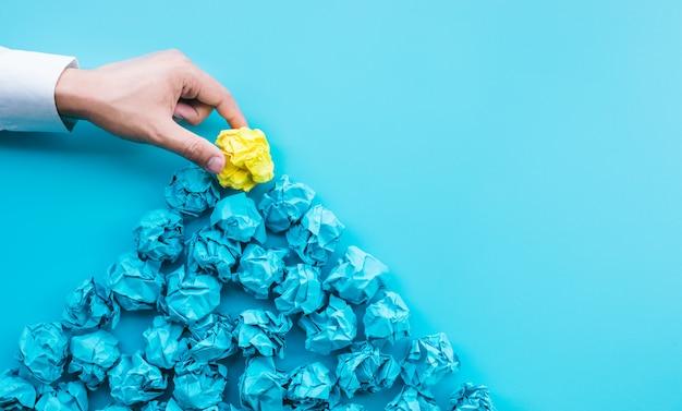 Pomysły i koncepcje kreatywności z osobą wybierającą wybitną zmiętą kulkę papieru