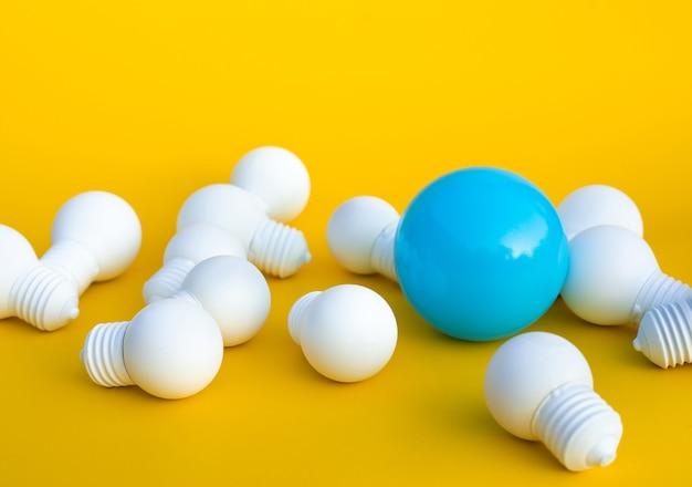 Pomysły, inspiracje, pomysły z wyróżniającym się tylko jednym balonem na grupie żarówek na niebieskim tle kreatywność biznesowa. motywacja do sukcesu. minimalistyczny styl.