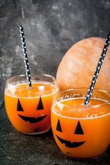 Pomysły na imprezę dla dzieci i halloween. dyniowy pomarańczowy koktajl w szkłach, ozdobiony latarnią z dyni, na czarnym kamiennym stole. skopiuj miejsce