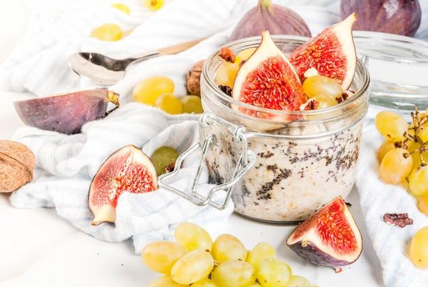 Pomysły na jesienne śniadanie, przepisy kulinarne. słoik nocnego owsa jesiennego z czerwonymi figami, winogronami i orzechami włoskimi. na białym