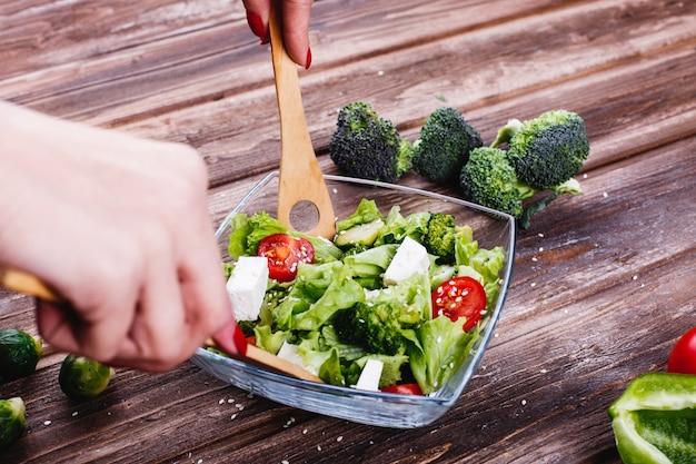 Pomysły na lunch lub kolację. kobieta wstrząsa świeżymi sałatkami zieleni, awokado, zielonym pieprzem
