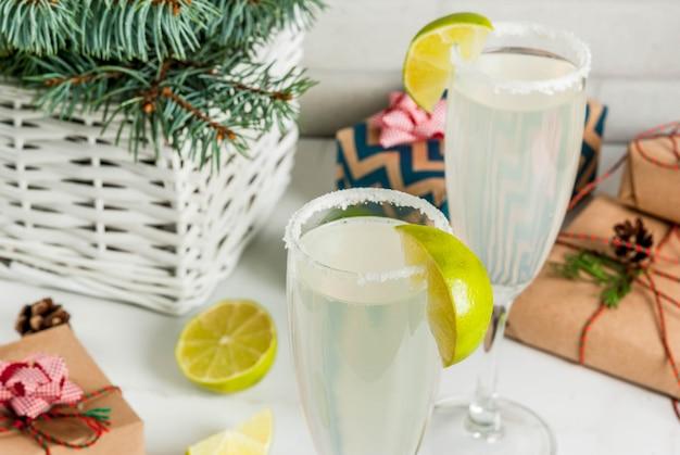 Pomysły na napoje świąteczne i noworoczne. koktajle margarita champagne, przyozdobione limonką i solą. na białym stole z dekoracjami świątecznymi, copyspace