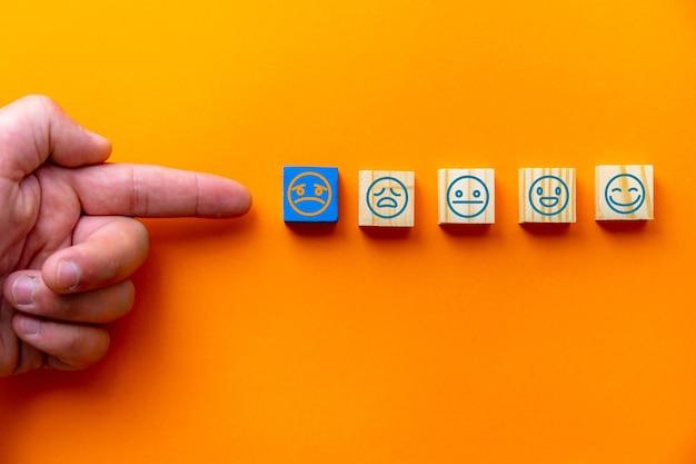 Pomysły na ocenę obsługi klienta i badania satysfakcji zostały wybrane ręką klienta na drewnianej kostce z niebieskim tłem.