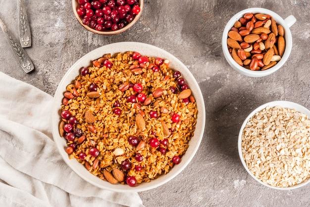 Pomysły na zimowe, jesienne śniadanie. święto dziękczynienia, . domowa granola gotowana ze świeżego miodu z migdałami orzechowymi, orzeszkami ziemnymi, orzechami laskowymi i żurawiną. na szarym betonowym stole widok z góry