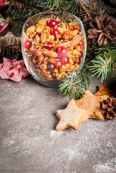 Pomysły na zimowe, jesienne śniadanie. święto dziękczynienia, . domowa granola gotowana ze świeżego miodu z migdałami orzechowymi, orzeszkami ziemnymi, orzechami laskowymi i żurawiną. w szklanym, szarym stole,