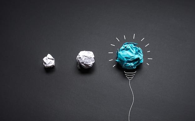 Pomysły z papierową zmiętą kulką z żarówką. kreatywność biznesowa i koncepcje rozwiązań