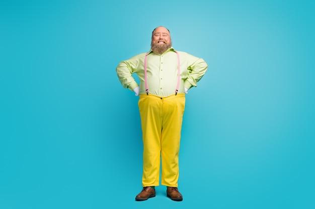 Ponadwymiarowy mężczyzna ubrany w dziwny wygląd stoi na niebieskim tle