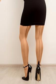 Pończochy na pięknych kobiecych nogach na wysokich obcasach.