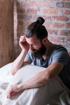 Poniedziałek rano. senność mężczyzna siedzący w łóżku. pocieranie oczu, wyglądanie na zmęczonego i sennego. mieszkanie na poddaszu.