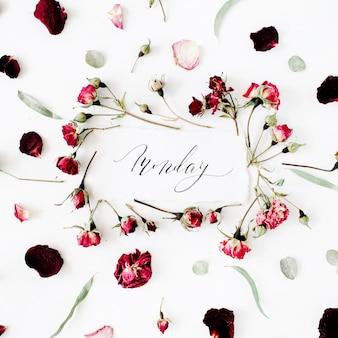Poniedziałek słowo napisane w stylu kaligrafii na papierze z różowymi, czerwonymi różami, eukaliptusem i liśćmi na białym tle