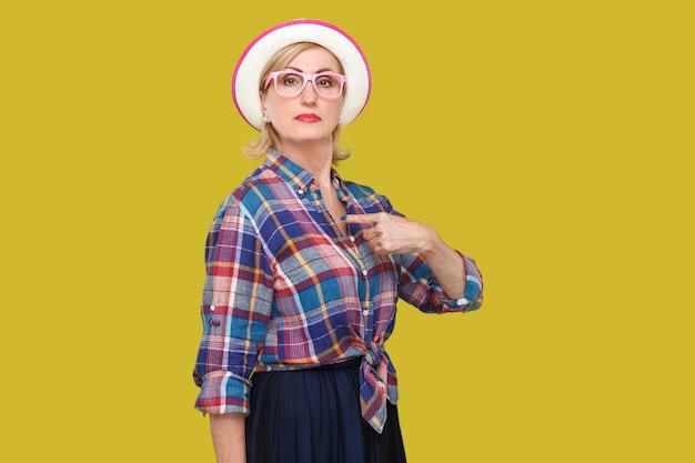 Ponieważ jestem. portret dumny poważny nowoczesny stylowy dojrzała kobieta w stylu casual z kapeluszem i okularami stojąc, wskazując siebie i patrząc na kamery. studio strzał na białym tle na żółtym tle.