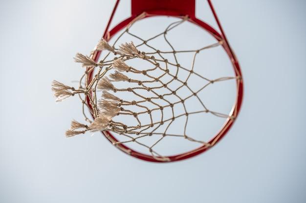 Poniżej widok kosza do gry w koszykówkę z jasnoniebieskim bezchmurnym niebem