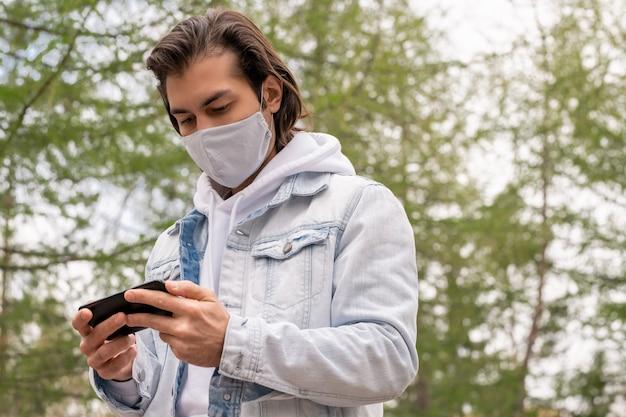 Poniżej widok mężczyzny w średnim wieku w masce z tkaniny i kurtce stojącego w parku i korzystającego z gadżetu