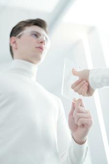 Poniżej widok młodego mężczyzny trzymającego skaner do uwierzytelniania linii papilarnych i sprawdzającego odcisk palca kobiety