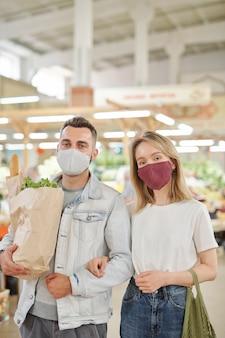 Poniżej widok młodej pary w maskach na twarz spacerującej razem po targu rolników podczas koronawirusa i kupującego jedzenie