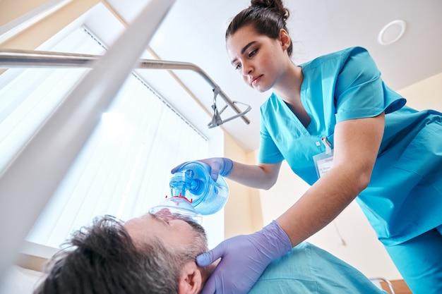 Poniżej widok młodej pielęgniarki w fartuchu i rękawiczkach chirurgicznych, używającej maski z wentylem workowym podczas ręcznej wentylacji