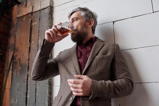 Poniżej widok zamyślonego, stylowego mężczyzny z brodą stojącego przy ścianie i popijającego whisky