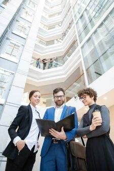 Poniżej widok zawartości zespołu młodych firm stojących w centrum biura i omawiających dane podczas analizy artykułów