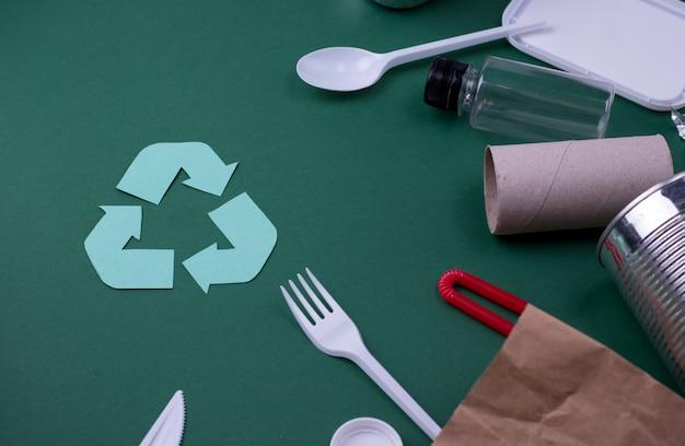 Ponowne użycie zmniejsza utylizację koncepcji płaskiego układania z odpadami plastiku, papieru i polietylenu. ekologia obraz ściany z symbolem recyklingu.