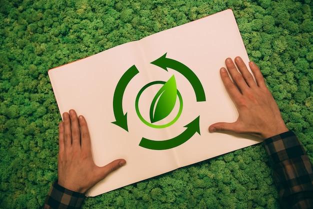 Ponowne zalesianie świata. widok z góry zbliżenie obrazu mężczyzny trzymającego się za ręce na swoim notatniku z symbolem strzałki i liścia na tle mchu