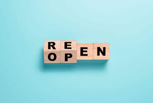 Ponownie otwórz ekran podziału tekstu na drewnianym bloku kostek. centrum handlowe i restauracje zostaną ponownie otwarte po covid 19.