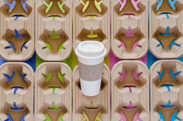 Ponownie użyj kubka do kawy z tuleją z papieru z recyklingu na tacach z recyklingu z kolorowym tłem. ponowne użycie i recykling w koncepcji środowiska na świecie.