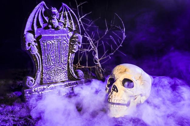 Ponura czaszka blisko nagrobku w mgle na ziemi