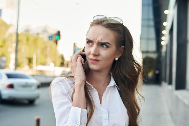 Ponura dziewczyna rozmawia na wyciągnięcie ręki. dziewczyna z telefonem śpieszy się.