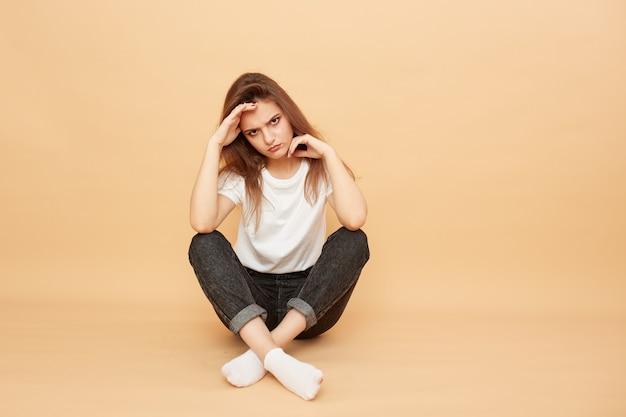 Ponura dziewczyna ubrana w białą koszulkę, jeansy i białe skarpetki siedzi na podłodze na beżowym tle w studio.