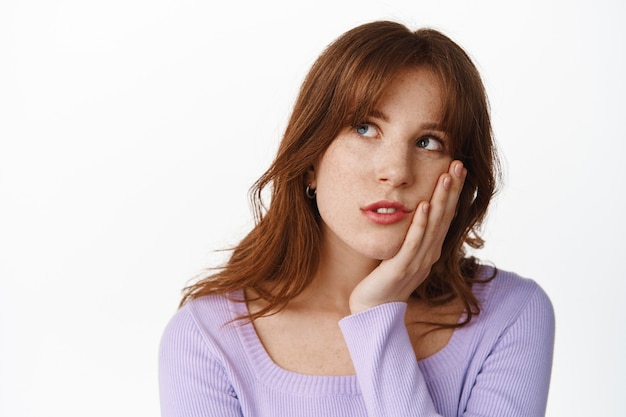 Ponura i znudzona młoda kobieta przewraca oczami, wpatrując się w lewy górny róg ze znudzonym, niezainteresowanym wyrazem twarzy, zmęczona czekaniem, stojąc na białym