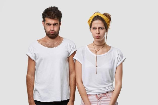 Ponura, ponura kobieta i mężczyzna dmuchają w policzek, nie rozmawiają ze sobą po kłótni, nie zgadzają się, obrażają złe słowa, stoją ramię w ramię w pomieszczeniu, noszą makietową białą swobodną koszulkę