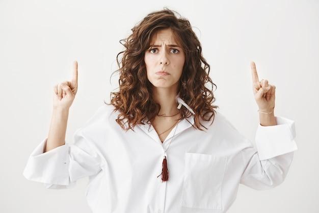 Ponura rozczarowana kobieta wskazuje palcami w górę smutno