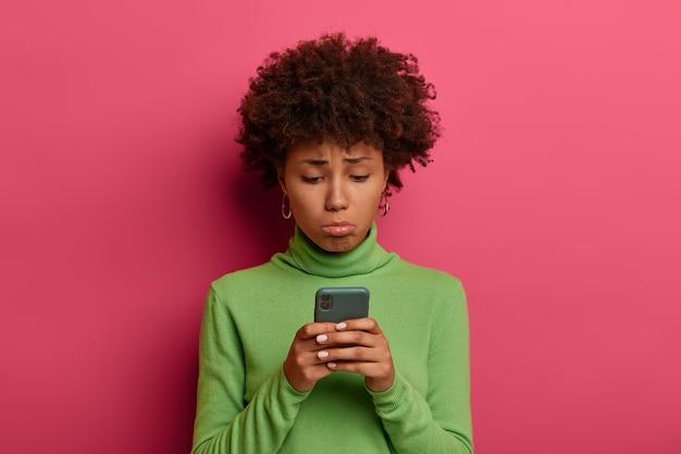 Ponura smutna kobieta czuje żal i niezadowolenie, zaciska dolną wargę, zdenerwowana, że nie otrzymała wiadomości od kochanka