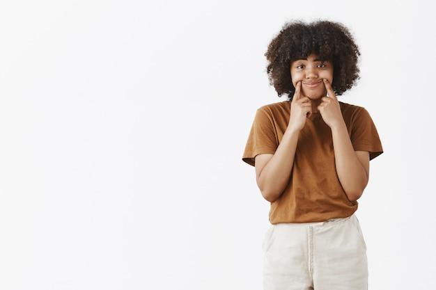 Ponura, zdenerwowana dziewczyna próbuje zwiększyć szczęście i rozweselić, ciągnąc kąciki ust, tworząc uśmiech na twarzy, czując się nieszczęśliwa i niezadowolona ze złej pogody, stojąca smutna nad szarą ścianą