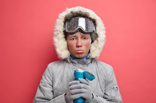 Ponura zmarznięta kobieta zaciska usta i wygląda na zdenerwowaną, czuje się zmęczona po zimowych sportach, pije gorący napój, aby ogrzać swoją nogawkę ubrana w płaszcz i rękawiczki podczas skitouringu narciarskiego.