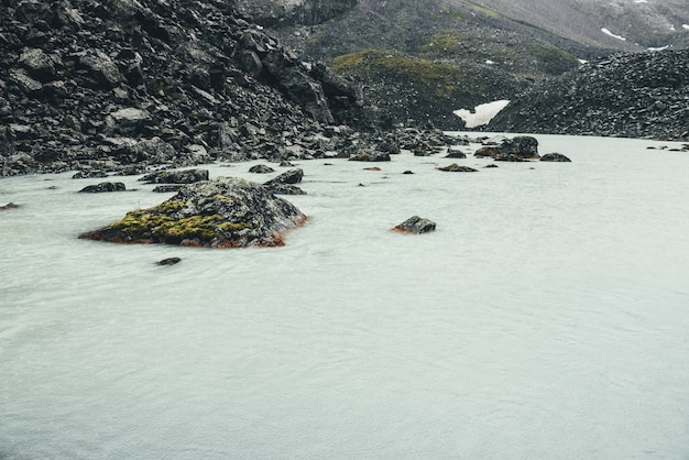 Ponury deszczowy krajobraz z kołami deszczu na powierzchni wody jeziora górskiego. klimatyczna górska sceneria z górskim jeziorem wśród moren w deszczową pogodę. duży głaz z mchem w jeziorze lodowcowym.