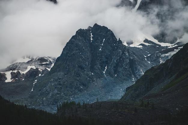 Ponury dramatyczny krajobraz alpejski z dużym klifem w niskiej chmurze w pobliżu gigantycznej śnieżnej góry ściany w ciemny wieczór. ciemna atmosferyczna sceneria ze śnieżnymi skałami w gęstej mgle. ogromny lodowiec za lasem na skałach.