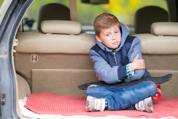 Ponury mały chłopiec siedzi w bagażniku samochodu typu hatchback, ściskając ramiona i krzywiąc się do kamery