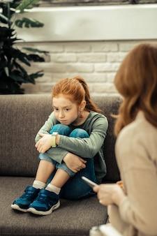Ponury nastrój. posępna nieszczęśliwa dziewczyna kładąca brodę na kolanach, myśląc o swoich problemach