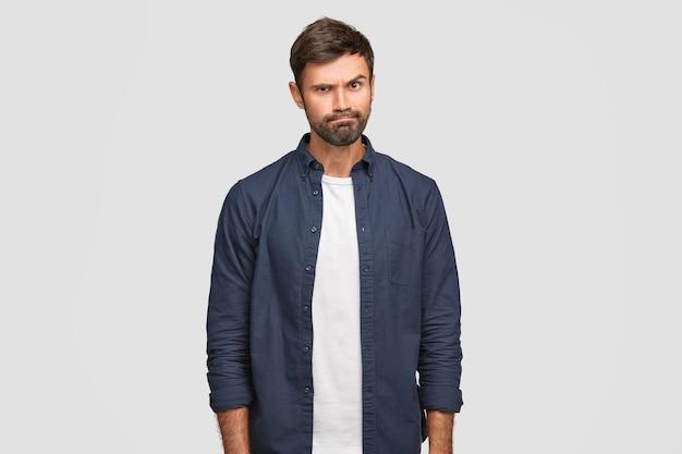 Ponury nieogolony facet ma zirytowany wyraz twarzy, unosi brwi i zaciska usta, czegoś nie lubi, wyraża niezadowolenie, nosi białą koszulkę i granatową koszulę, pozuje samotnie
