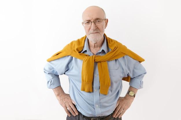 Ponury niezadowolony starszy biznesmen z łysą brodą w okularach, zegarku i swetrze na formalnej koszuli pozuje przy białej ścianie, trzymając ręce na talii, niezadowolony z pracy swoich pracowników