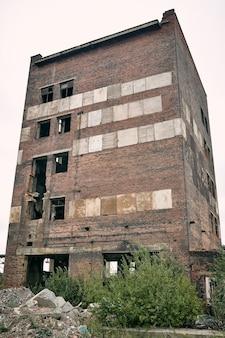 Ponury, opuszczony budynek z cegły z powybijanymi oknami i krzakami, kamienie wokół pierwszego piętra