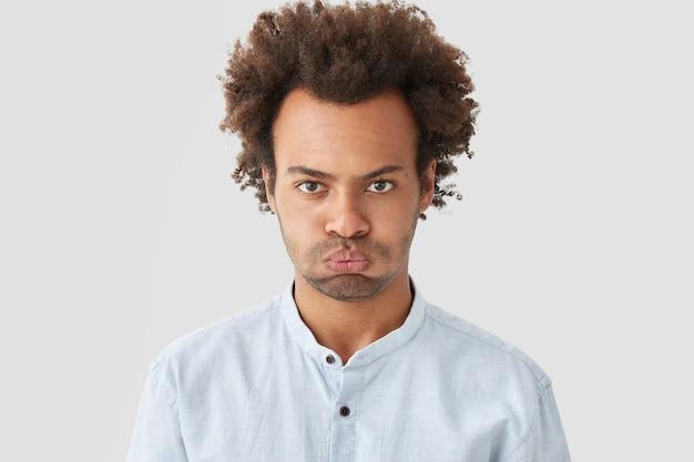 Ponury posępny mężczyzna z kręconymi włosami, zarostem, niezadowolonym wyrazem twarzy, wyrażający negatywne emocje, ubrany w białą koszulę