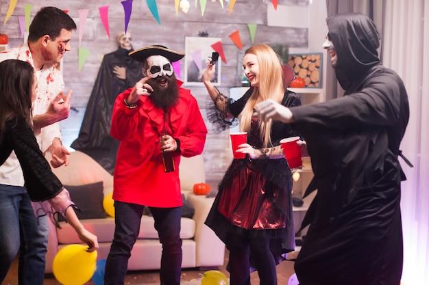 Ponury żniwiarz i pirat tańczą podczas świętowania halloween. upiorne kostiumy.