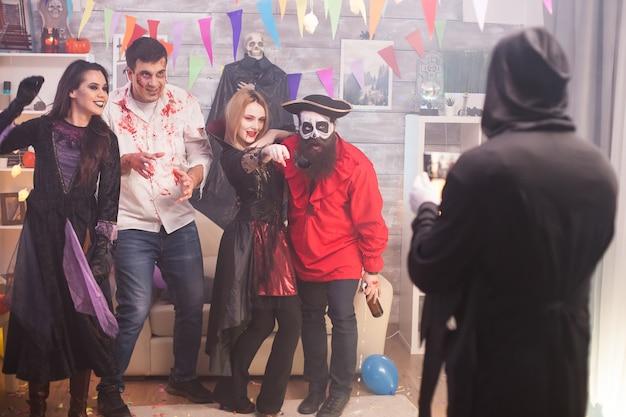 Ponury żniwiarz robiący zdjęcia piratowi i jego przyjaciołom na imprezie z okazji halloween.