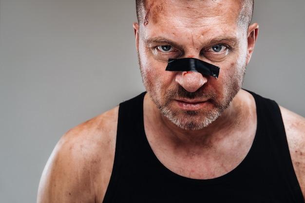 Poobijany mężczyzna w czarnej koszulce wyglądający jak wojownik i przygotowujący się do walki