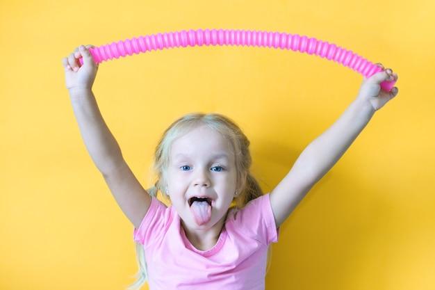 Pop rura. plastikowa zabawka antystresowa sensoryczna z tuby pop w rękach dziecka. wesoła dziewczynka bawi się zabawkami fidget pop rury. trend 2021 r. żółte tło