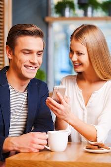 Popatrz na to zdjęcie! piękna młoda kobieta pokazująca coś na telefonie komórkowym swojemu chłopakowi podczas wspólnego picia kawy w kawiarni