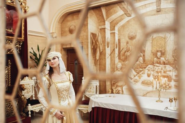 Popatrz przez słupki w małej księżniczce w fancy ubrania